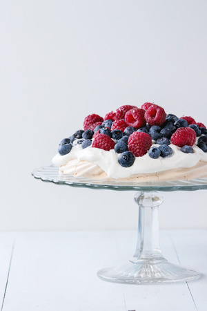 dessert stand: Vintage cake stand with Meringue dessert Pavlova with fresh blackberries and raspberries, over blue wooden table. Stock Photo