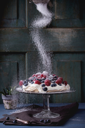 sugar powder: Vintage cake stand with Meringue dessert Pavlova with fresh blackberries and raspberries, strewing by sugar powder. Over blue wooden table. Dark rustic style.