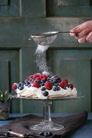 dessert stand: Vintage cake stand with Meringue dessert Pavlova with fresh blackberries and raspberries, strewing by sugar powder. Over blue wooden table. Dark rustic style.