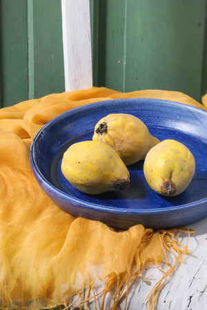 quinces: Three quinces in blue ceramic plate with orange textile on old white wooden chair with green wooden wall at background. Stock Photo