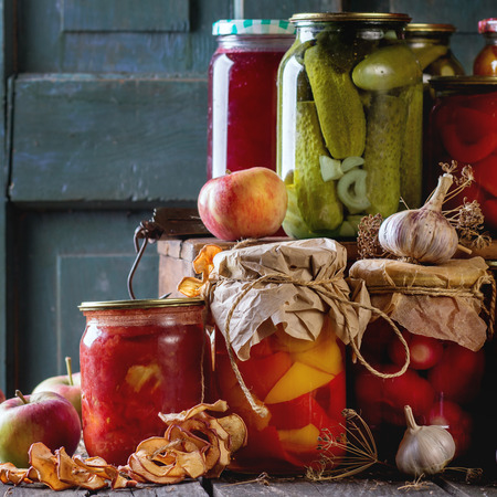 Collection set of many homemade glass jars with preserved food (cucumbers, tomatoes, peppers), with garlic and fresh and dried apples. Over old wooden table. Dark rustic style. Square image Banco de Imagens