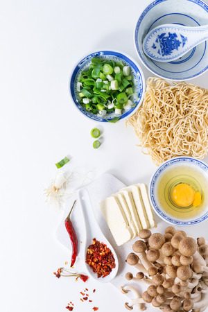 Ingredients for asian ramen soup. Noodles, spring onion, feta cheese, mushrooms, egg and chili pepper in asian porcelan bowls over white kitchen table. Top view 版權商用圖片