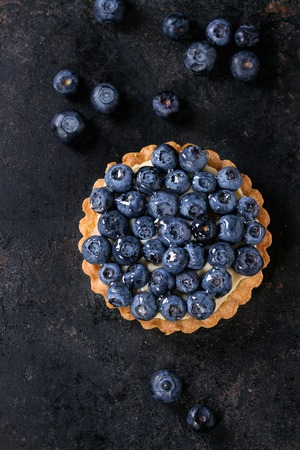 recipe decorated: Lemon tartlet with fresh blueberries over black background. Top view. With space for text