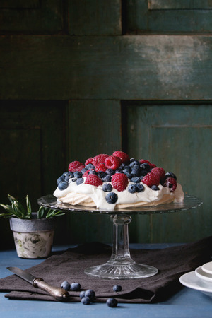 dessert stand: Vintage cake stand with Meringue dessert Pavlova with fresh blackberries and raspberries. Over blue wooden table with old tableware, textile napkin and snowdrops flowers. Dark rustic style. Stock Photo