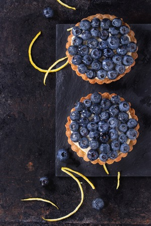 recipe decorated: Two Lemon tartlets with fresh blueberries, served on black stone slate with lemon and lemon zest over black background. Top view. With space for text