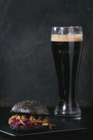 meat and alternatives: Black homemade burger with beef stews and red cabbage served on black square plate with glass of dark beer over wooden table with black background.
