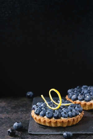 recipe decorated: Two Lemon tartlets with fresh blueberries, served on black stone slate with lemon and lemon zest over black background.