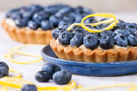recipe decorated: Close up of Two Lemon tartlets with fresh blueberries, served on blue ceramic plate over white textile background. Stock Photo