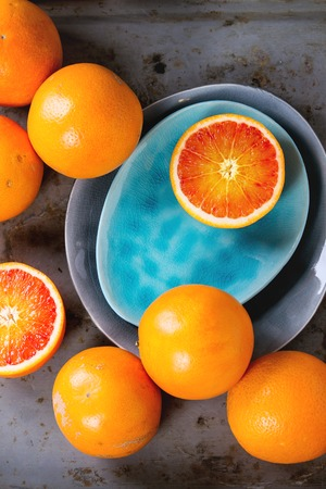 ovoid: Sliced and whole Sicilian Blood orange fruit on bright turquoise and gray ceramic plates over rusty metal background. Flat lay