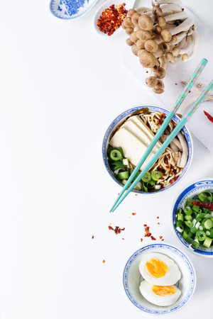 Chinese porcelain bowl of asian ramen soup with feta cheese, noodles, spring onion and mushrooms, served with turquoise chopsticks and sliced egg over white background. Top view