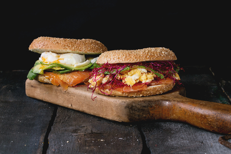 Two Bagels with salted salmon, spinach, beetroot sprouts, avocado scrambled and soft boiled egg with liquid yolk on wooden chopping board over old wood black background.