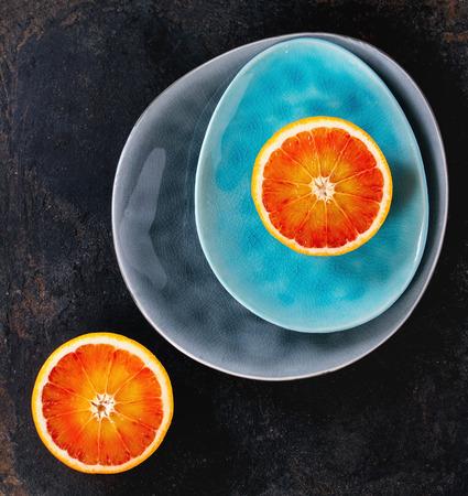 ovoid: Sliced Sicilian Blood orange fruit on bright turquoise and gray ceramic plates over black background. Flat lay Stock Photo