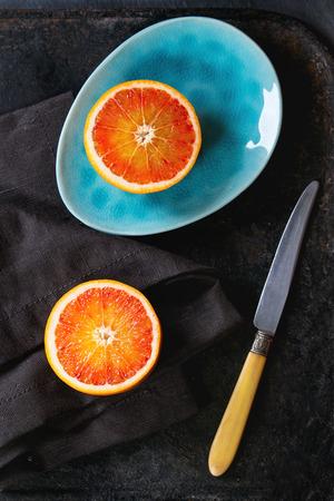 ovoid: Sliced Sicilian Blood orange fruit on bright turquoise ceramic plates over black background, with vintage knife and textile napkin. Flat lay Stock Photo