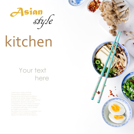 Chinese porcelain bowl of asian ramen soup with feta cheese, noodles, spring onion and mushrooms, served with turquoise chopsticks and sliced egg over white background. Top view. With sample text