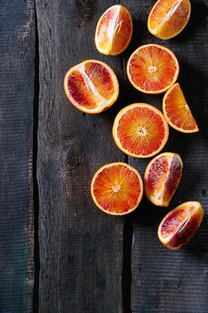 Sliced Sicilian Blood oranges fruits over old dark wooden background. Top view