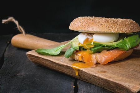 liquid: Bagel with salted salmon, spinach, avocado and soft boiled egg with liquid yolk on wooden chopping board over old wood black background. Stock Photo