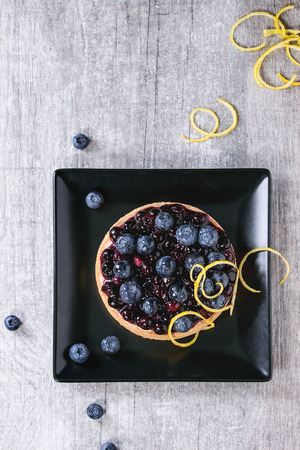 recipe decorated: Round Lemon Tart with fresh and cooked blueberries, served on black square plate with lemon zest over gray wooden background. Flat lay. With space for text Stock Photo