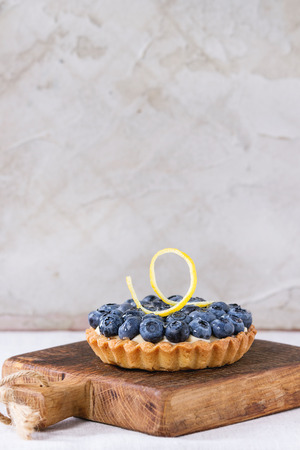 recipe decorated: Lemon tartlet with fresh blueberrie and lemon zest, served on small wooden chopping board over white table.