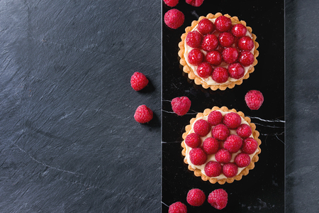 Two Tartlets with custard and fresh ripe raspberries, served on black marble board over stone slate surface. With copy space at left. Top view
