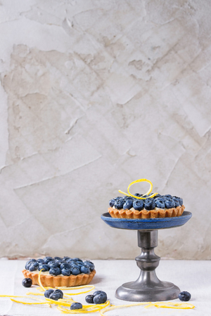 recipe decorated: Lemon tartlet with fresh blueberries and lemon zest, served on vintage cake stand over white tablecloth. Stock Photo