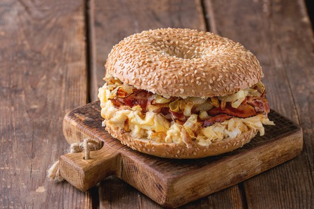 Bagel with bacon, scrambled eggs and fried onion on small wooden chopping board over wooden background. 版權商用圖片