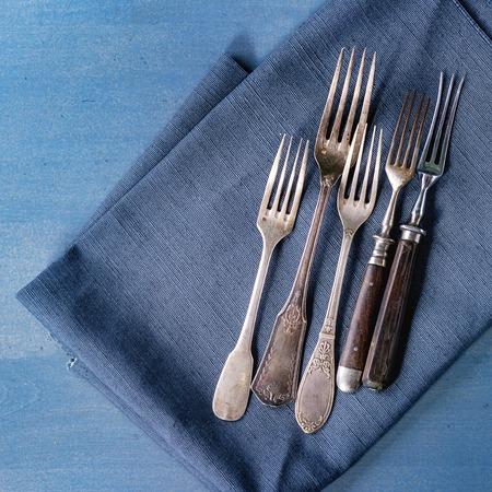 grunge flatware: Set of vintage forks on blue textile napkin over blue wooden surface. Top view