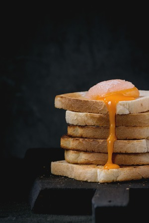 sugared: Pile of toasts bread with flowing sugared yolk on black wooden cutting board over black textured background.