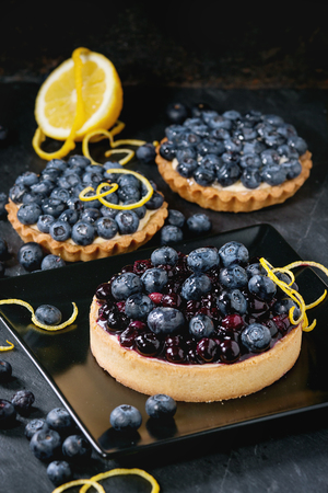 recipe decorated: Lemon Tart and tartlets with fresh and cooked blueberries, served on black square plate with lemon and lemon zest over black background.