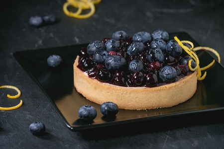 recipe decorated: Round Lemon Tart with fresh and cooked blueberries, served on black square plate with lemon zest over black background.