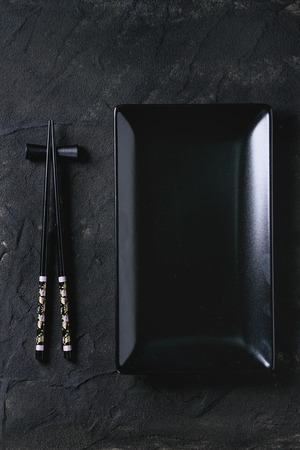 Black painted chopstics on chopsticks rest and empty square plate over black textured surface. Flat lay.