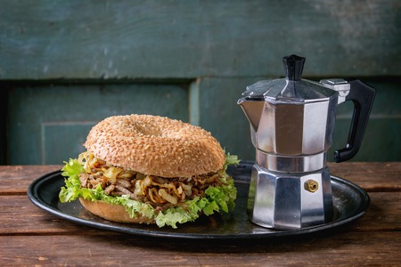coffee pot: Bagel with stew beef, fresh salad and fried onion served on vintage metal tray with coffee pot over wooden table. Stock Photo