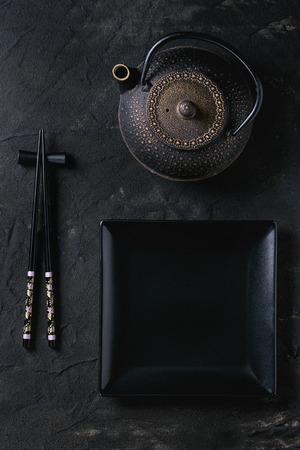 Black painted chopstics on chopsticks rest, empty square plate and iron teapot over black textured surface. Flat lay.