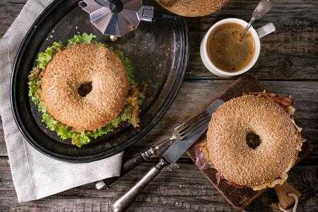 carne de res: Dos panecillos con estofado de carne, ensalada fresca, tocino, huevos revueltos y cebolla frita que se presentan en la bandeja de metal de la vendimia con la taza de café y la cafetera sobre la mesa de madera. aplanada Foto de archivo