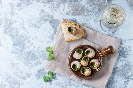 alcochol: Escargots de Bourgogne - Snails with herbs butter, in traditional ceramic pan with parsley, bread and glass of white wine on textile napkin over blue textured background. Top view, copy space Stock Photo