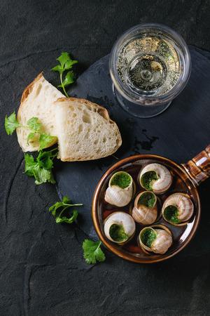 CARACOL: Escargots de Bourgogne - Caracoles con mantequilla de hierbas, plato gourmet, en el molde de cer�mica tradicional con el perejil, el pan y la copa de vino blanco a bordo de piedra de pizarra sobre el fondo negro con textura. Vista superior Foto de archivo
