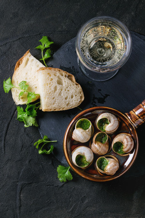 alcochol: Escargots de Bourgogne - Snails with herbs butter, gourmet dish, in traditional ceramic pan with parsley, bread and glass of white wine on stone slate board over black textured background. Top view