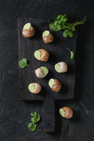 Uncooked Escargots de Bourgogne - Snails with herbs butter, gourmet dish, on black wooden chopping board with parsley over black textured background. Top view.