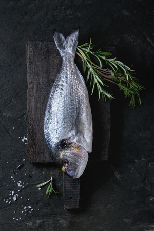 dorade: Two ready to cook raw bream fish with rosemary herbs and sea salt on wooden cutting board over black textured background. Top view