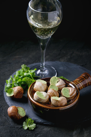 alcochol: Uncooked Escargots de Bourgogne - Snails with herbs butter, gourmet dish, in traditional ceramic pan with parsley and glass of white wine on stone slate board over black textured background. Stock Photo