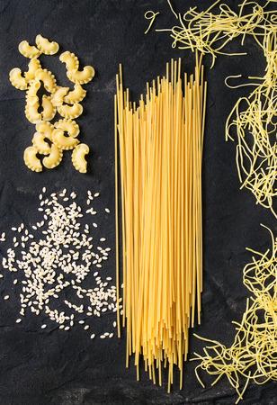 gallo: Assortment of dry pasta spaghetti, orzo, noodles and creste di gallo over black textured background. Top view