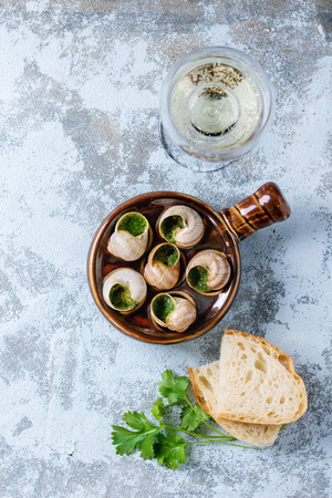 alcochol: Escargots de Bourgogne - Snails with herbs butter, in traditional ceramic pan with parsley, bread and glass of white wine over blue textured background. Top view, copy space Stock Photo