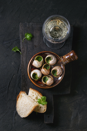 alcochol: Escargots de Bourgogne - Snails with herbs butter, in traditional ceramic pan with parsley, bread and glass of white wine on wooden chopping board over black textured background. Top view Stock Photo