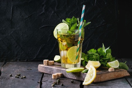 alcochol: Glass of Iced green tea with lime, lemon, mint and sugar cubes on wooden chopping board over old wooden table. Dark rustic style.