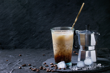 Glass of ice coffee with cream and milk, served with coffee beans, ice cubes and coffee pot on slate stone board over black textured background.