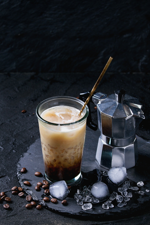 cold background: Glass of ice coffee with cream and milk, served with coffee beans, ice cubes and coffee pot on slate stone board over black textured background.