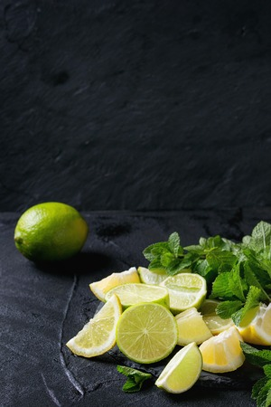 over black: Sliced Lime and lemons with bunch of fresh mint on black slate stone board over black textured background Stock Photo