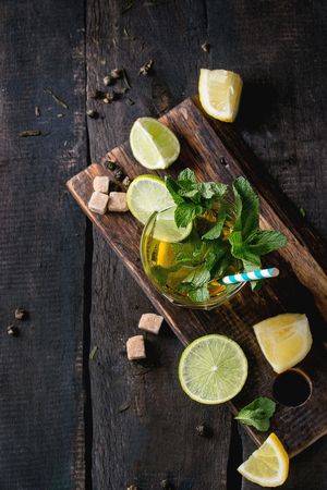 alcochol: Glass of Iced green tea with lime, lemon, mint and sugar cubes on wooden chopping board over old wooden table. Dark rustic style. Flat lay