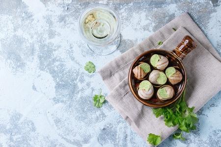alcochol: Uncooked Escargots de Bourgogne - Snails with herbs butter, gourmet dish, in traditional ceramic pan with parsley and glass of white wine over blue textured background. Top view.