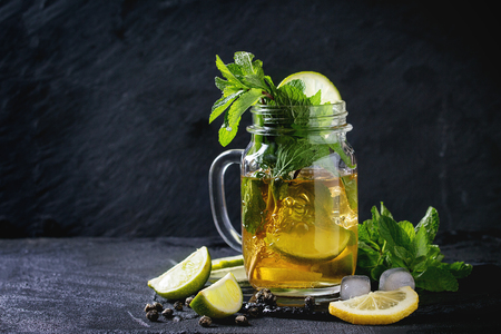 Glass mason jar of Ice green tea with lime, lemon, mint and ice cubes on black slate stone board over black textured background. With copy space Stock Photo