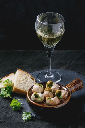 alcochol: Escargots de Bourgogne - Snails with herbs butter, gourmet dish, in traditional ceramic pan with parsley, bread and glass of white wine on stone slate board over black textured background.